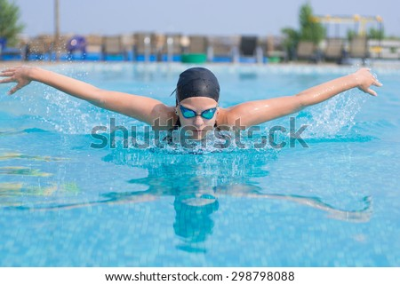 Young girl in goggles and cap swimming butterfly stroke style in the blue water pool - stock photo