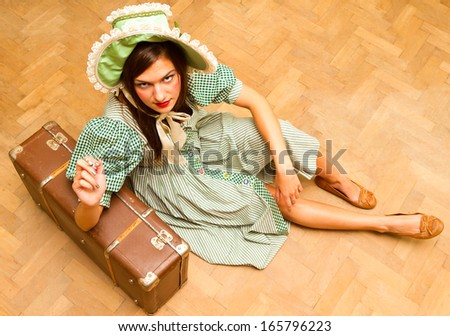 young girl in green dress sitting on the floor with a suitcase, vintage style