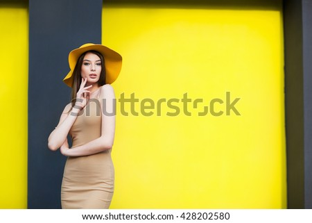 Young girl in hat posing by the yellow wall - stock photo