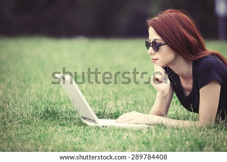 Young girl in indie style clothes with laptop computer on green grass in the park