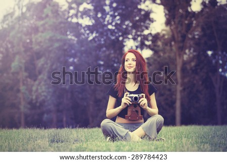 Young girl in indie style clothes with retro camera on green grass in the park