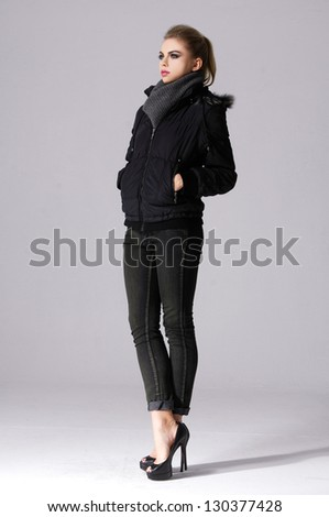 young girl in jacket with scarf standing posing on white background - stock photo