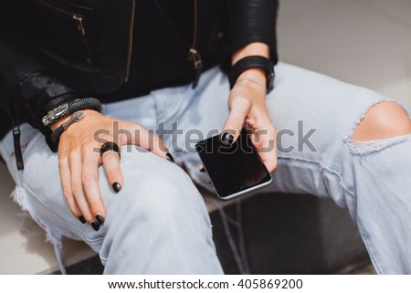 young girl in jeans and a leather jacket on the street and holding a smart phone, writes letters, answers the phone, checks in mail, Internet, screen touch, touch, outdoor portrait, - stock photo