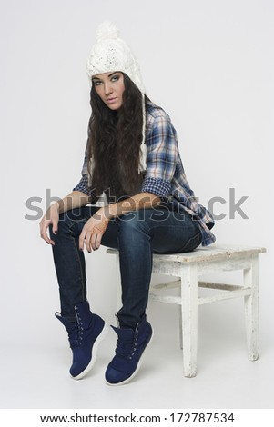 Young girl in jeans, shirt and hat sits on a stool in the studio. Isolated on a light background. - stock photo