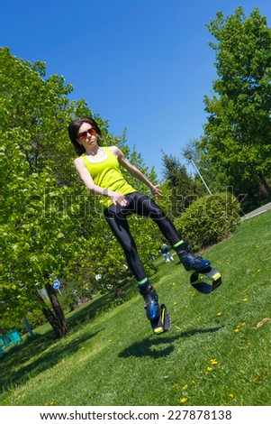 young girl in jumping boots doing fitness outdoors - stock photo