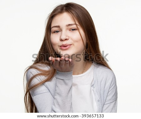 Young girl in light jacket sending an air kiss, isolated on white background