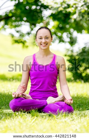 Young girl in lotus pose in the park. girl sitting in the lotus position on grass - stock photo