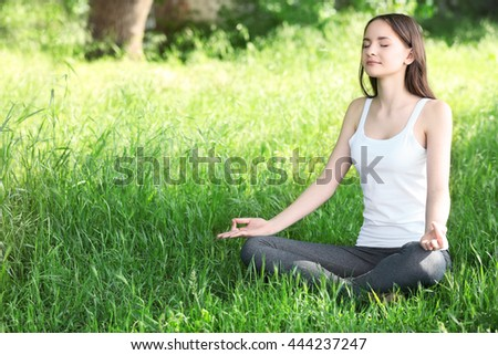 Young girl in lotus position on green meadow