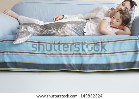 Young girl in mermaid costume sleeping on sofa with mother at home - stock photo