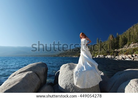 Young girl in mom's wedding dress overlooking beautiful Lake Tahoe.