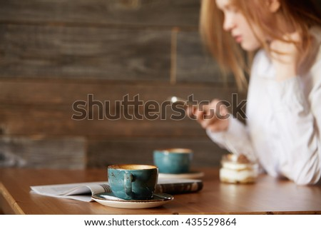 Young girl in office clothes checking out her social networks in a stylish café, typing on device. Caucasian woman waiting for her business partner with two cups of coffee and newspaper on the table. - stock photo