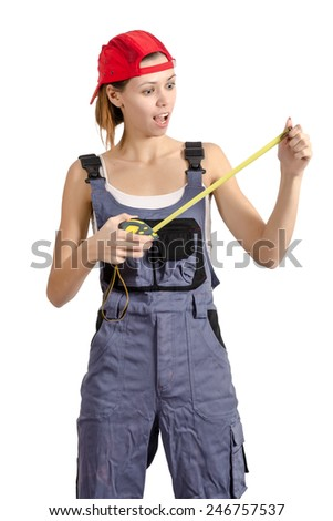 Young girl in overalls looking at building a tape measure in hand. Isolated on white