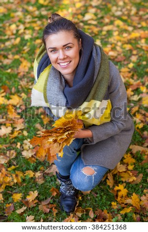 Young girl in park with bouquet of leaves. Autumn time