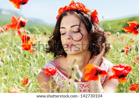 Young girl  in poppies field - stock photo