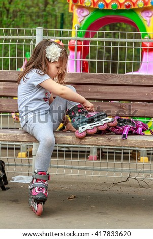 young girl in protective equipment and rollers in park, outdoor portrait - stock photo