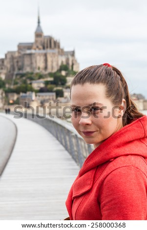 Young girl in red coat in Mont Saint Michel, France - stock photo