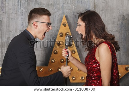 Young girl in red cocktail dress and guy singing with vintage microphone