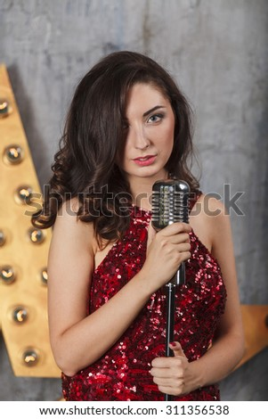 Young girl in red cocktail dress singing with vintage microphone