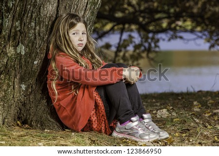 young girl, in red outfit leaning against a tree. A look of sadness or thought on her face, close up full body shot with lake in the background blurred. - stock photo