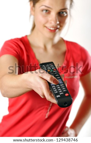 young girl in red watching tv using a remote control