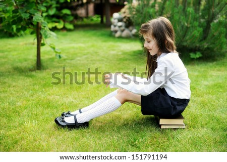 Young girl in school uniform sitting on stack of books