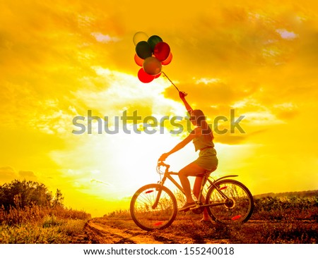 Young Girl in sexy dress with sunglasses riding bicycle  flying air balloons on leash yellow sun set sky background Copy space for inscription SYMBOL OF EASE  - stock photo