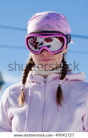Young girl in ski mask on winter sport resort in european mountains - stock photo