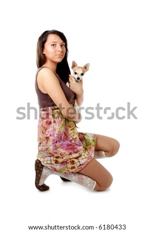 Young girl in skirt and ballet slippers holding chihuahua