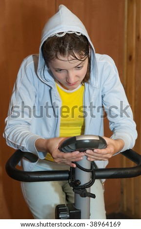 Young girl in sportswear exercising on exercise bike - stock photo
