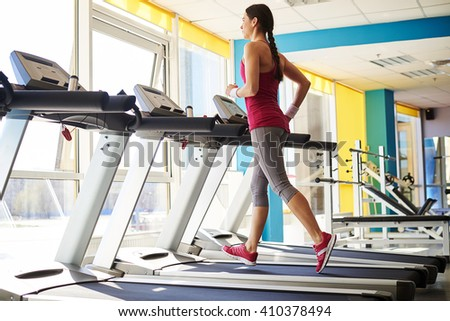 Young girl in sportswear is running on a treadmill