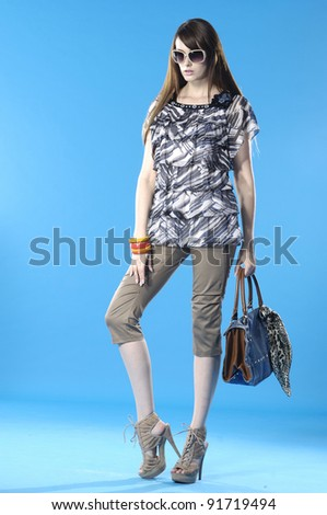 young girl in spring fashion dress wearing sunglasses with handbag posing - stock photo