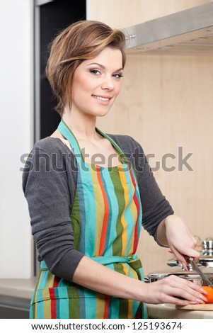 Young girl in striped apron cooks vegetables in the modern comfortable kitchen - stock photo