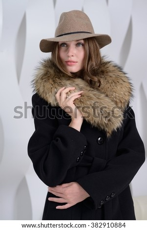 Young girl in studio posing at coat