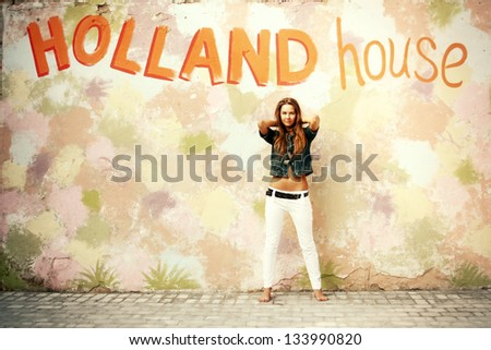 Young girl in summer outdoor posing against painted colorful wall - stock photo