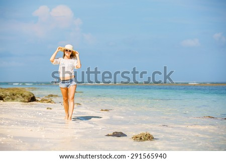 Young girl in sunglasses and a hat relaxing near the sea and enjoying her summer vacation. Travel, vacation, paradise concept, copyspace