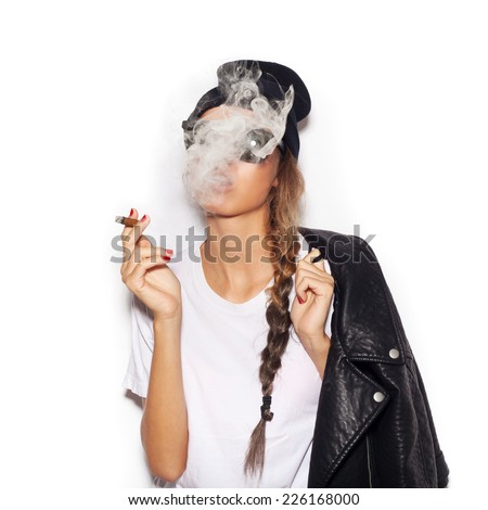 Young girl in sunglasses and black leather jacket smoking cigar.  White background, not isolated - stock photo