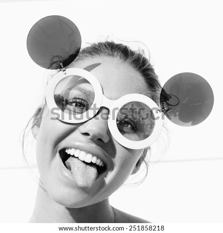 young girl in sunglasses showing tongue. hipster have fun. teen. lifestyle. Toned black and white - stock photo