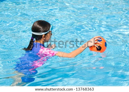 Young girl in swimming pool playing with rubber ball