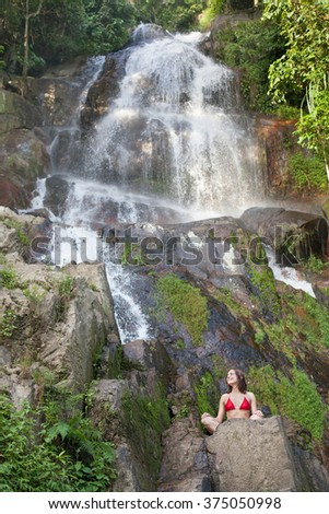 Young girl in swimsuit, is doing yoga on tropical waterfall. - stock photo