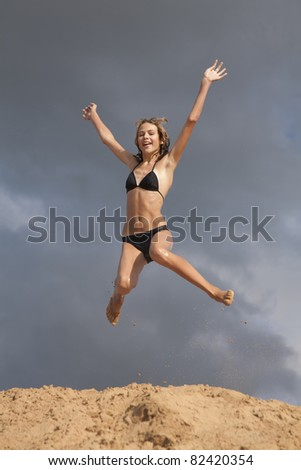 Young girl in swimsuit jumps above the sands embankment against blue sky