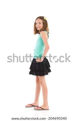 Young girl in teal shirt and black skirt posing with flower in her hair. Full length studio shot isolated on white. - stock photo
