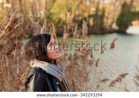 Young girl in the autumn park near the lake