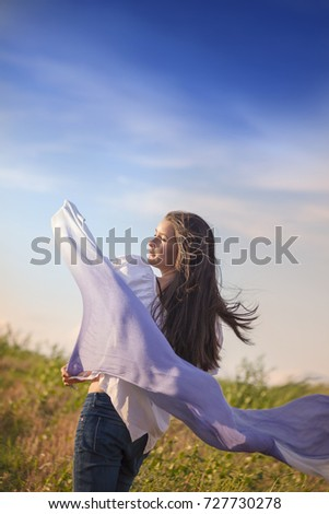 Young girl in the field with blue scarf