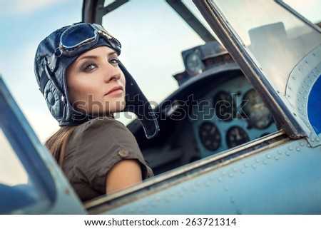 Young girl in the flying suit in the cockpit - stock photo