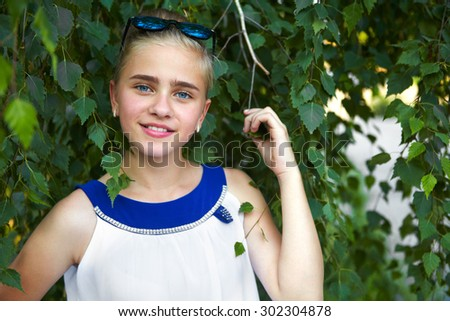 Young girl in the garden. Tree birch