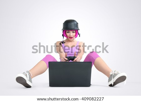Young girl in the helmet with joystick sits on the floor and playing game on a laptop