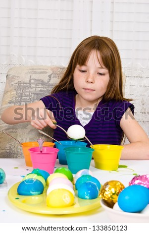 Young girl in the process of coloring Easter Eggs - Step two, the egg on a spoon about to be lowered into the cup of dye