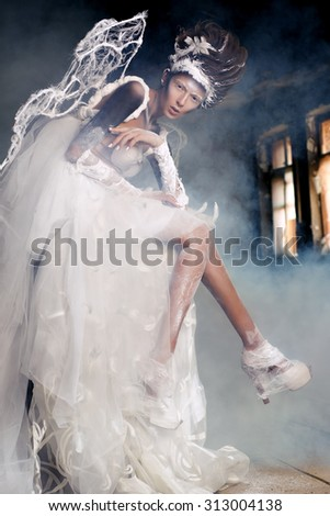 Young girl in the similitude of angel with stylish makeup  in the abandoned building