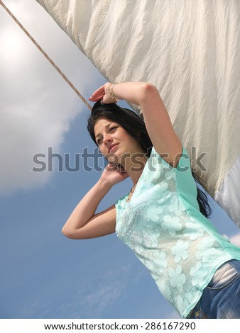 young girl in the sunshine on a background of sky and sails - stock photo