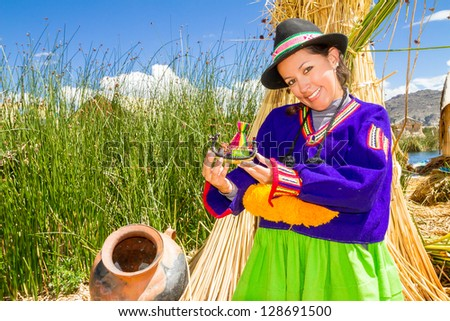 Young girl in traditional indian costume with traditional handcrafts, on a floating Uros island Peru - stock photo